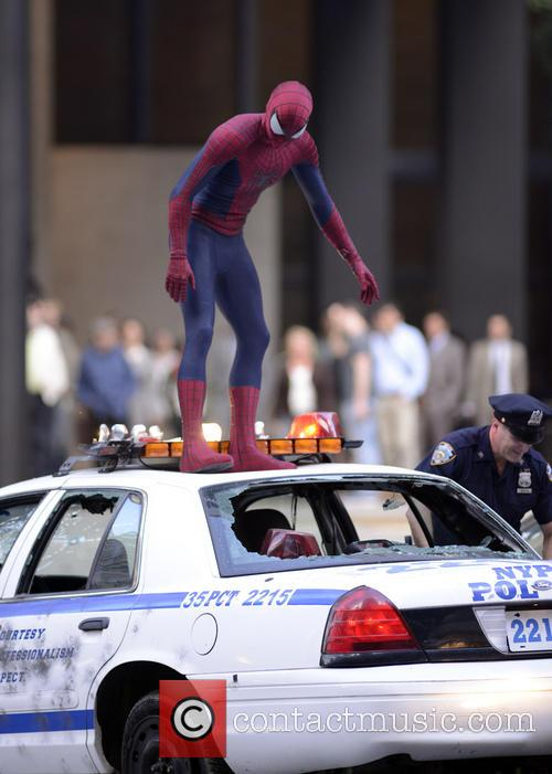 Spider Man atop a ruined cop car