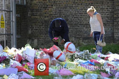 Members of the public lay flowers and pay...