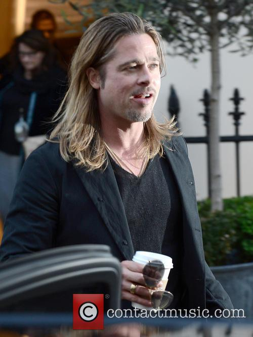 Brad Pitt, holding a cup of coffee, leaves...