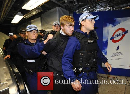A G8 protester is arrested by police at...