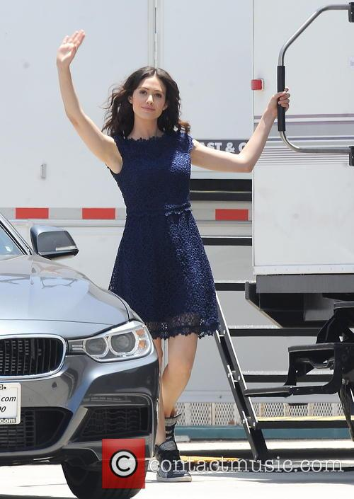 Rossum sports a blue dress with sneakers on the set of her new comedy