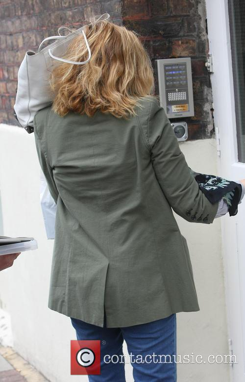 Actress Kim Cattrall covers her face with her...