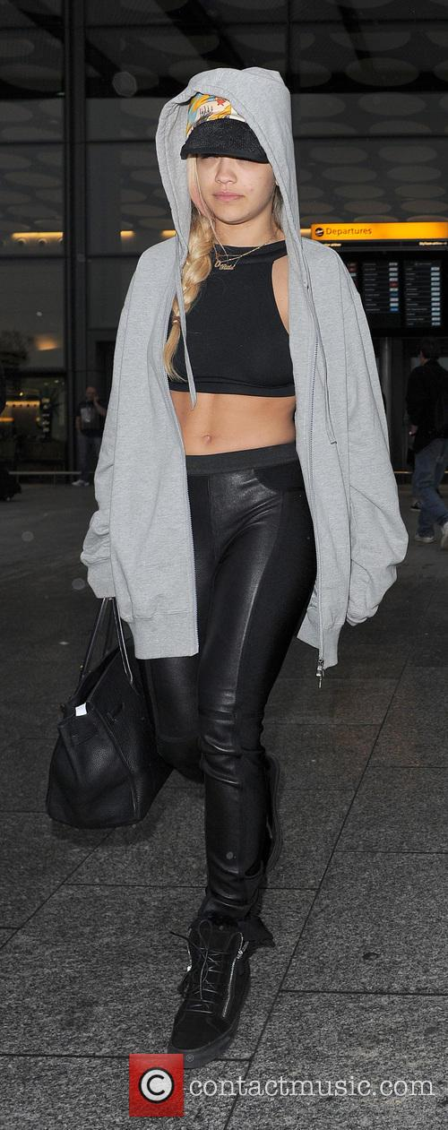 A rather camera-shy Rita Ora arrives at Heathrow Airport on a flight from Malta