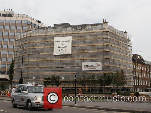 A sign hangs on a building scaffold in...