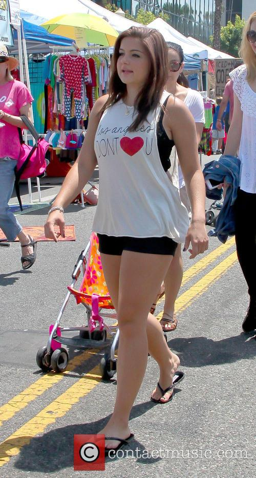 Ariel Winter sits in a stroller