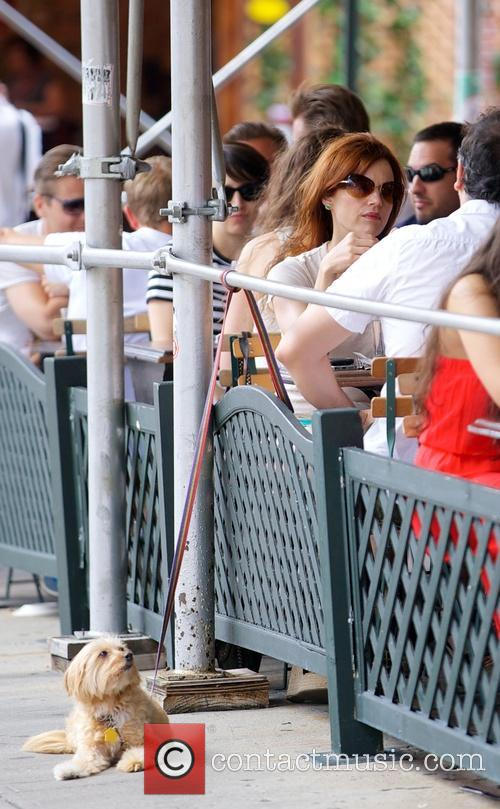 Carla Gugino sitting at an outdoor cafe