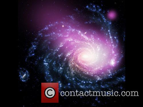 Dwarf Galaxy caught ramming into a large spiral...