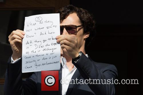 Benedict Cumberbatch holds up a sign in protest