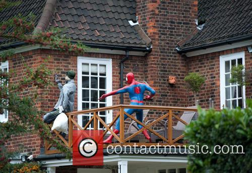 Spider-Man is seen chasing a crooked burglar off...