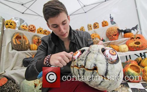 A street vendor paints and carves Halloween pumpkins...