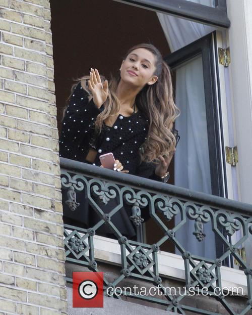 Ariana Grande waves to fans from her hotel...