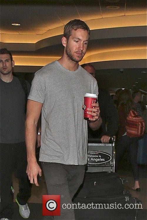 Calvin Harris arrives at LAX airport carrying a...