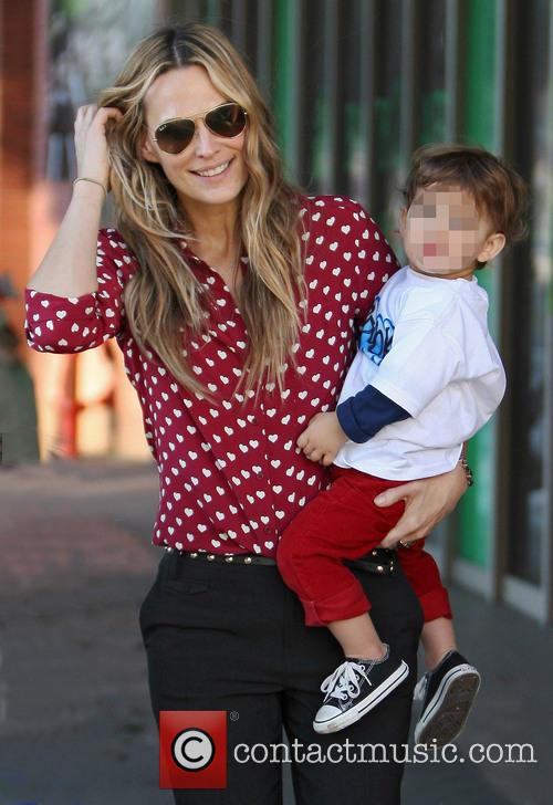 Molly Sims carries her son Brooks as she...