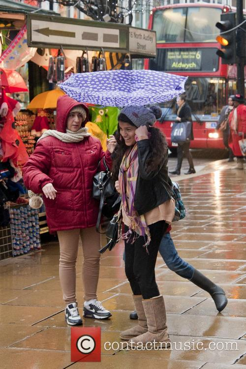 Christmas shoppers on Oxford Street with umbrellas