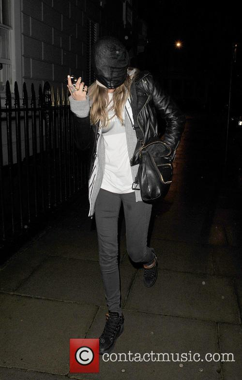 Cara Delevingne returns home, wearing what appears to be a pair of tights over her head!