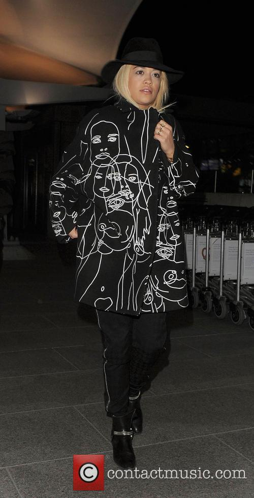 Rita Ora arrives back in England at Heathrow...