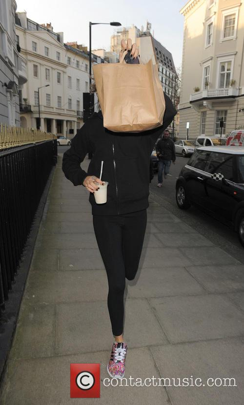 Cara Delevingne returns home covering her face with...