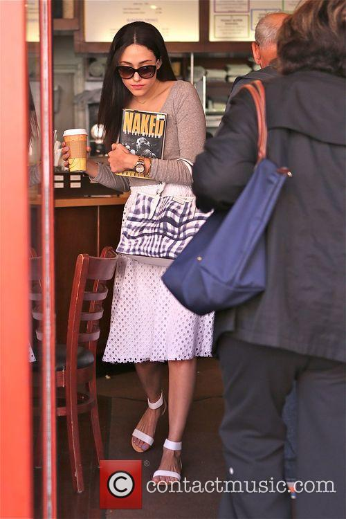Emmy Rossum picks up a cup of coffee