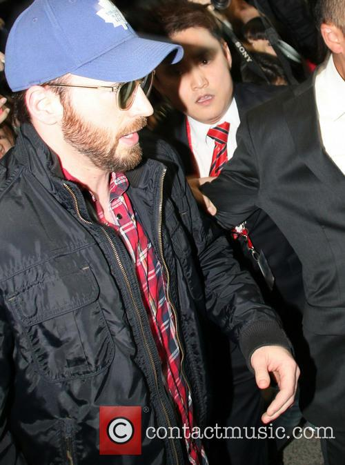 Chris Evans is ushered by security through Incheon...