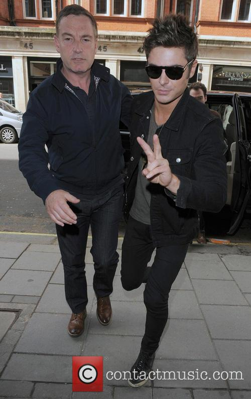Zac Efron returning to his hotel, flanked by...