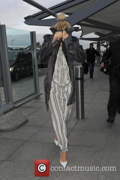 Rita Ora and her tour manager catch an early flight from Heathrow Airport