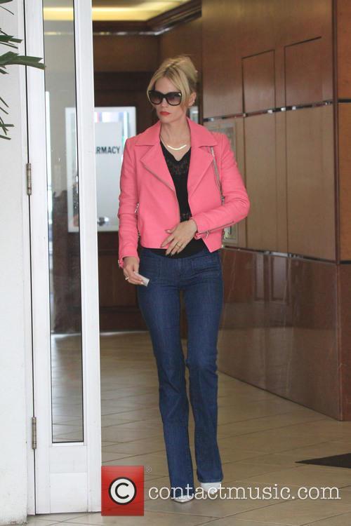 January Jones wears a hot pink jacket out...