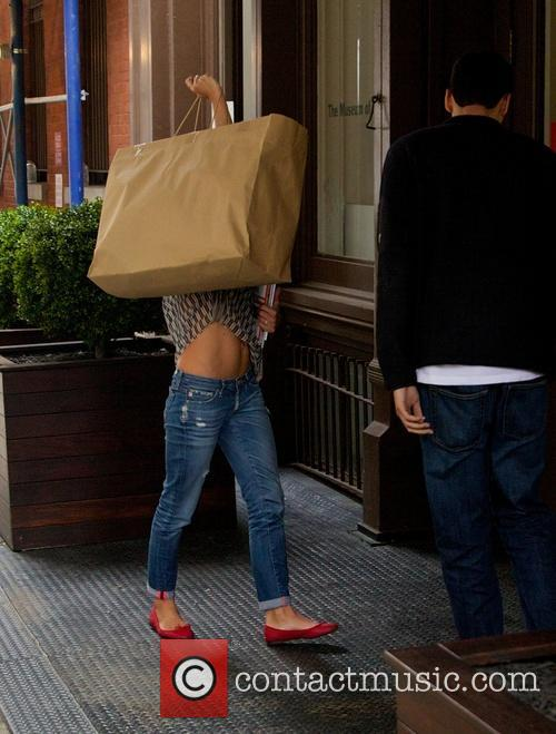 Kelly Ripa hides her face while out in...