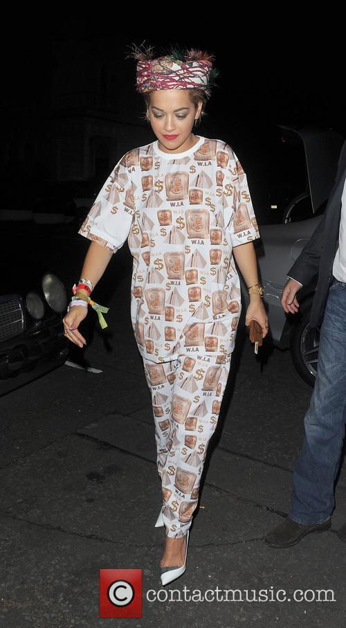 Rita Ora arriving at a studio, wearing a jumpsuit covered in dollar signs, and a headscarf