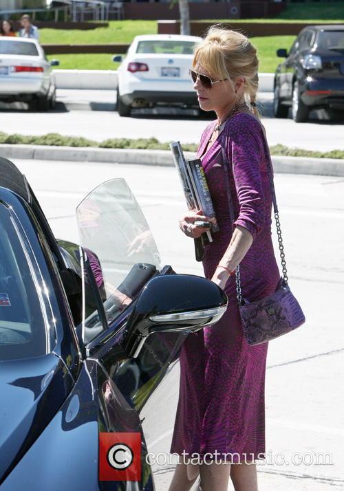 Melanie Griffith wearing a long purple patterned dress...