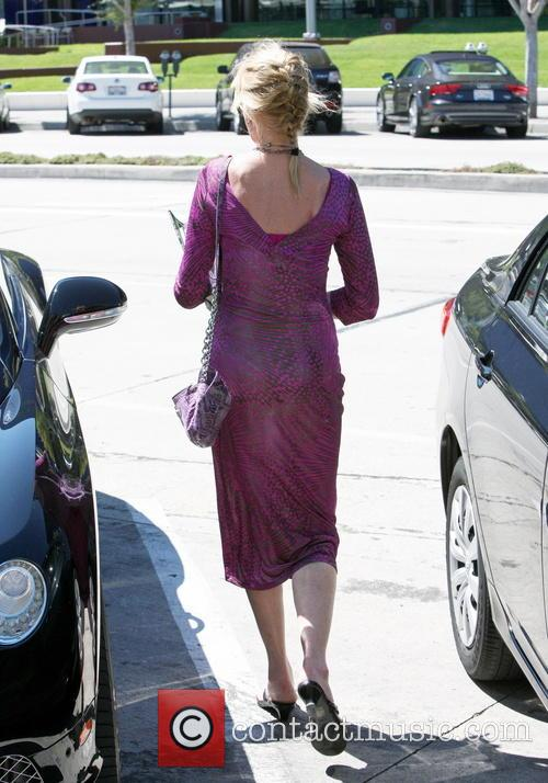 Melanie Griffith wearing a long purple patterned dress and smoking a cigarette at Pacific Design Center