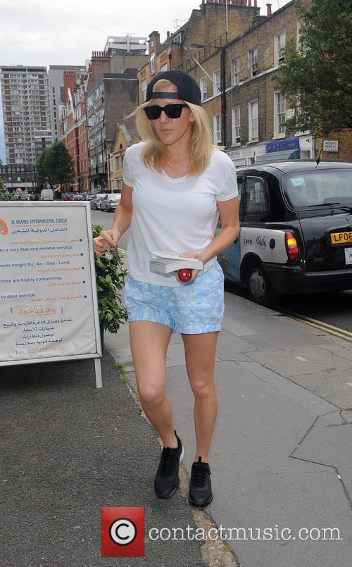 Ellie Goulding arrives home, wearing baggy shorts with...