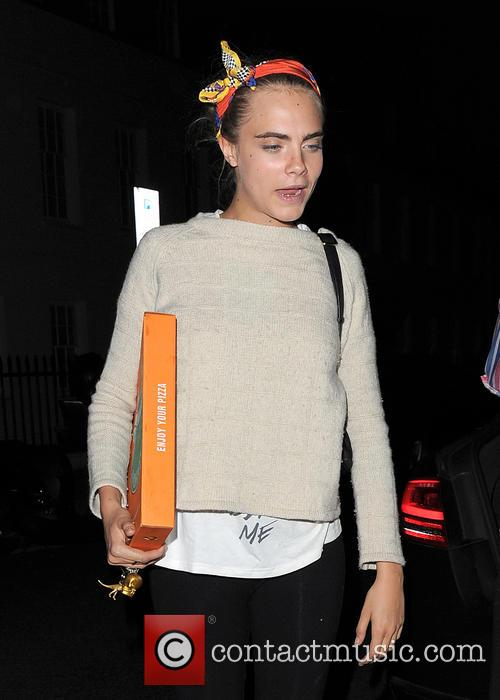 Cara Delevingne arrives home carrying a takeaway pizza