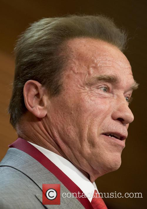Arnold Schwarzenegger receives a medal honoring him as...
