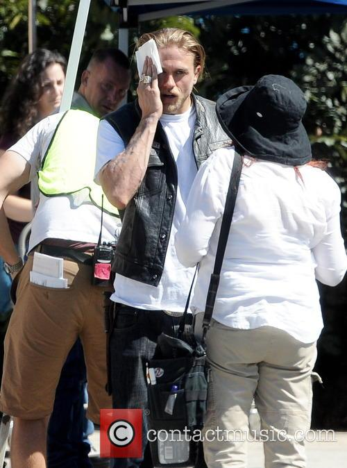 Charlie Hunnam carrying a gun on the set...
