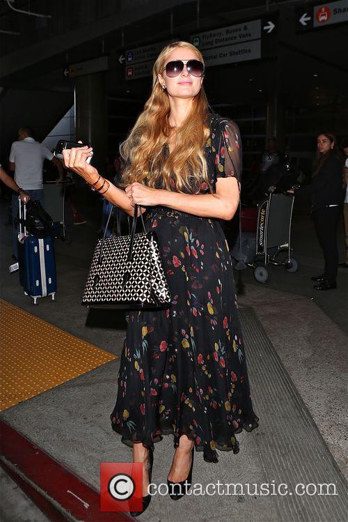 Paris Hilton looks happy as she shows off...