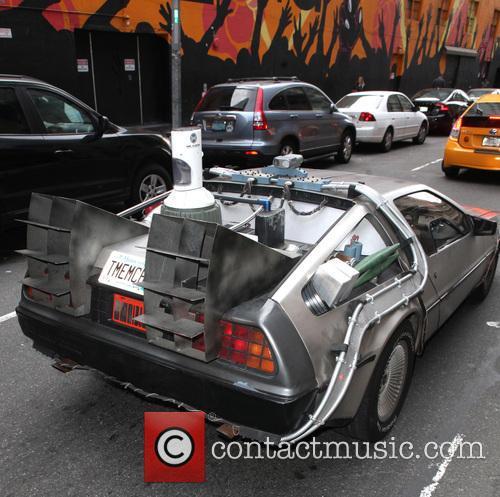 A DeLorean DMC-12 drives along a road in...