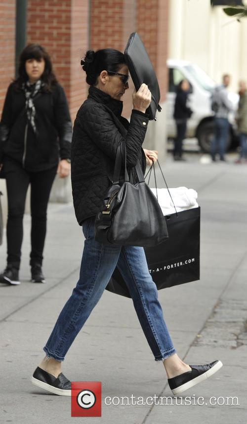 A camera shy Julianna Margulies attempts to hide...