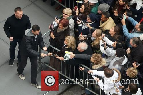 Hugh Jackman signs autographs with a bandaged thumb...