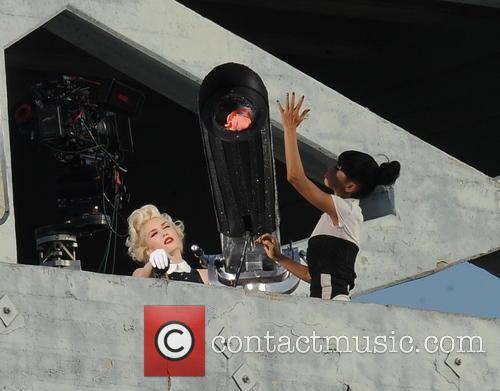 Gwen Stefani mans an giant cannon while filming...