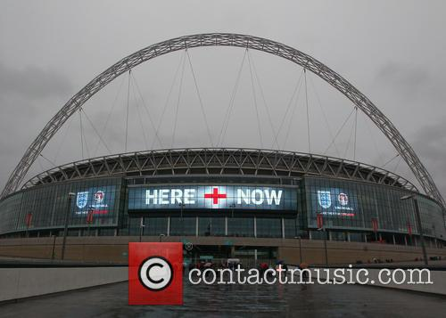 Fans arrive at Wembley Stadium for the first...