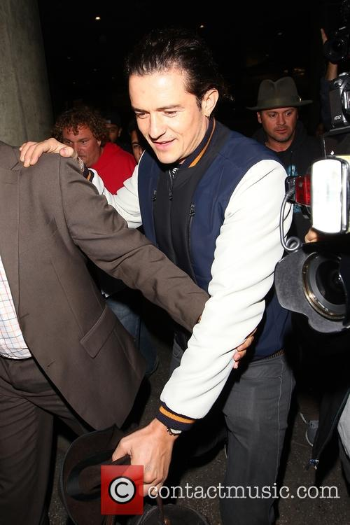 Orlando Bloom is surrounded by fans as he...