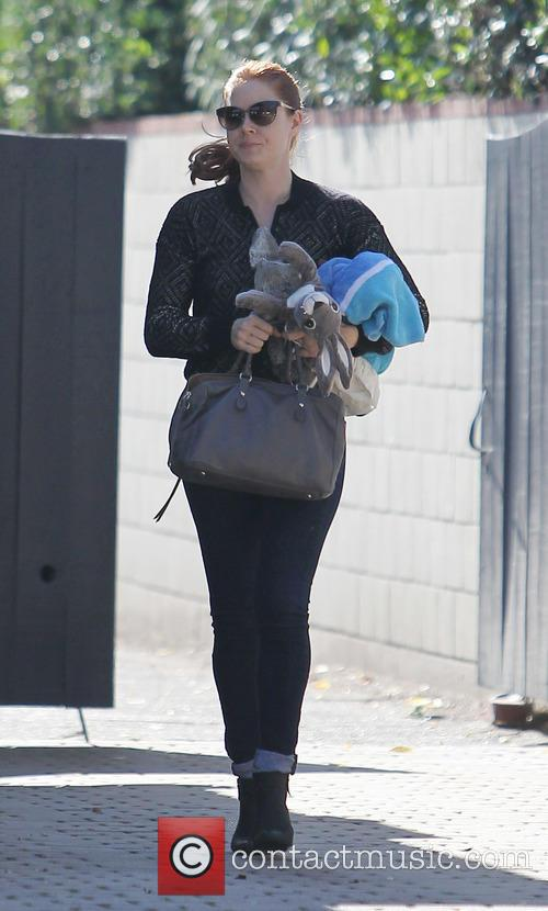 Amy Adams carries a plush rabbit while out...