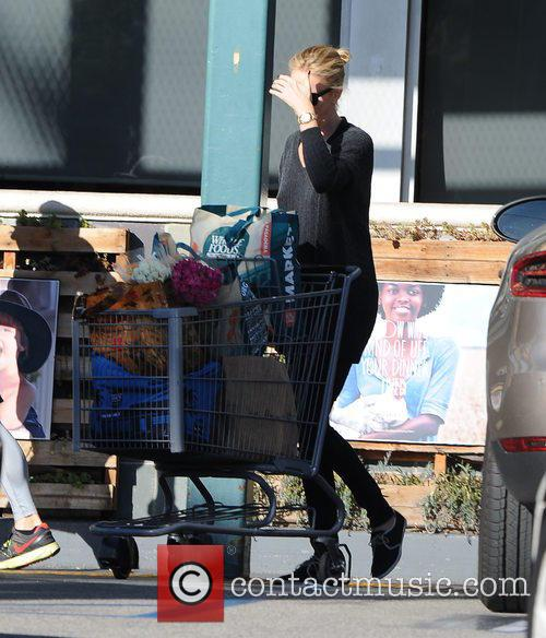 A very camera-shy Charlize Theron goes food shopping