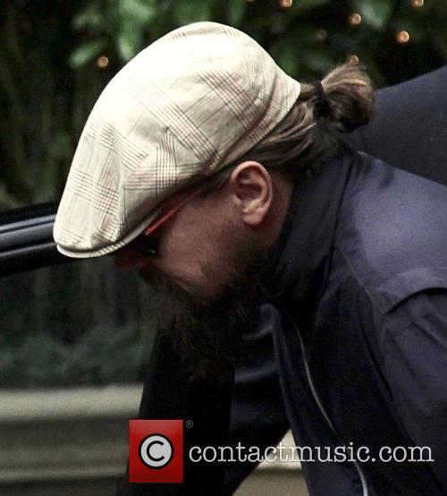 Leonardo DiCaprio jumps quickly into a car