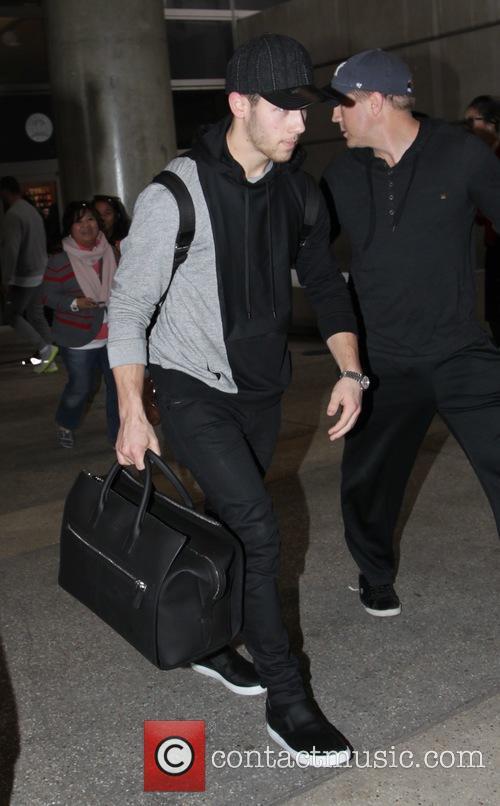Nick Jonas arrives at Los Angeles International Airport...