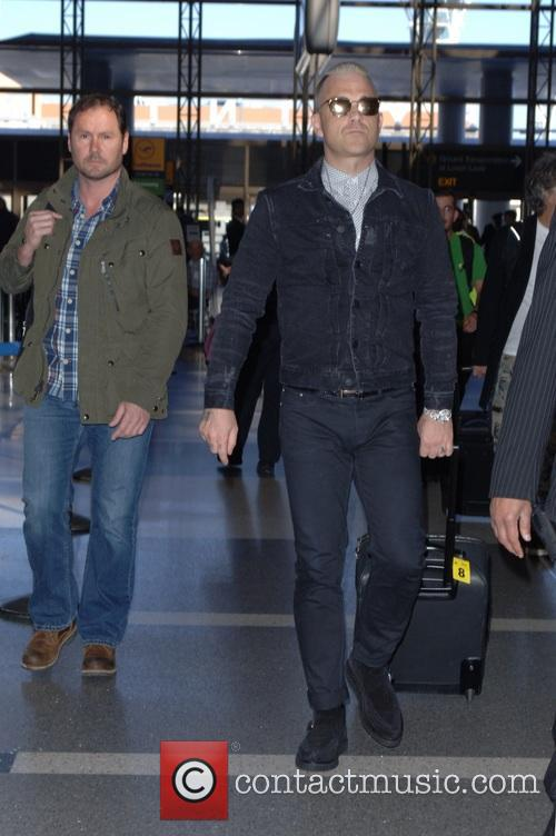 Robbie Williams arrives at Tom Bradley International to...