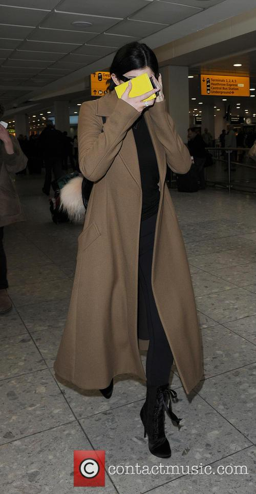 Kylie Jenner arriving at Heathrow Airport, covering her...