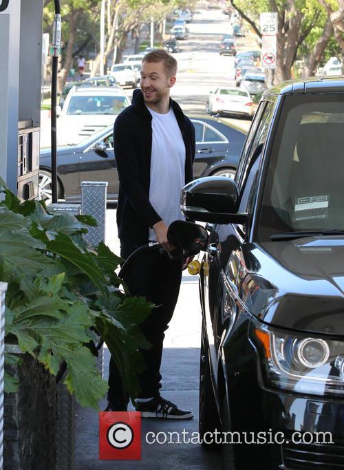 Calvin Harris pumping gas at a garage in...