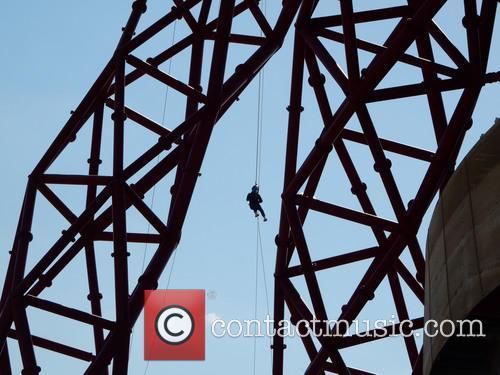A man abseils down The Orbit