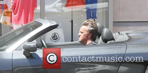 Matthew Perry smokes a cigarette while driving